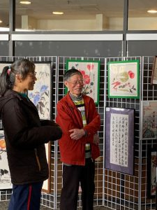 People discussing artwork at Brush Painting Calligraphy exhibit